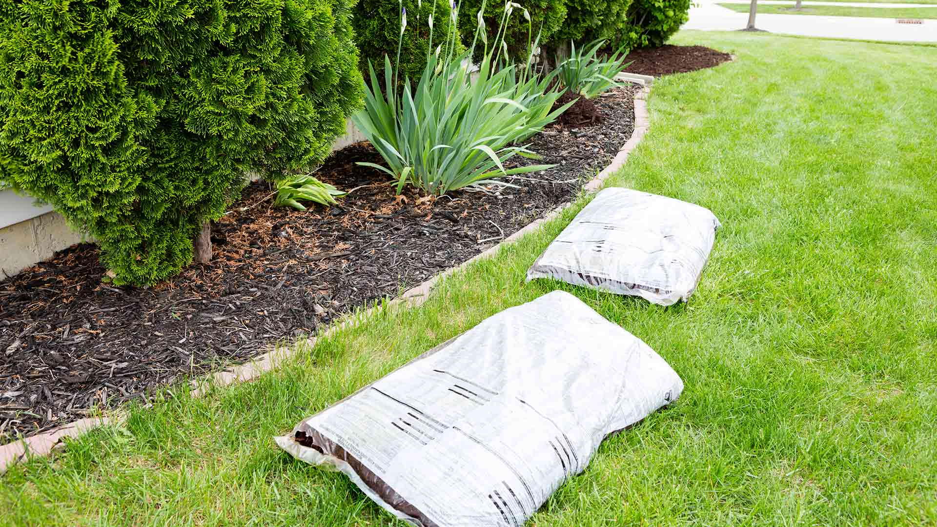 Two mulch bags that will be opened to replenish the landscape bed of a homeowner.